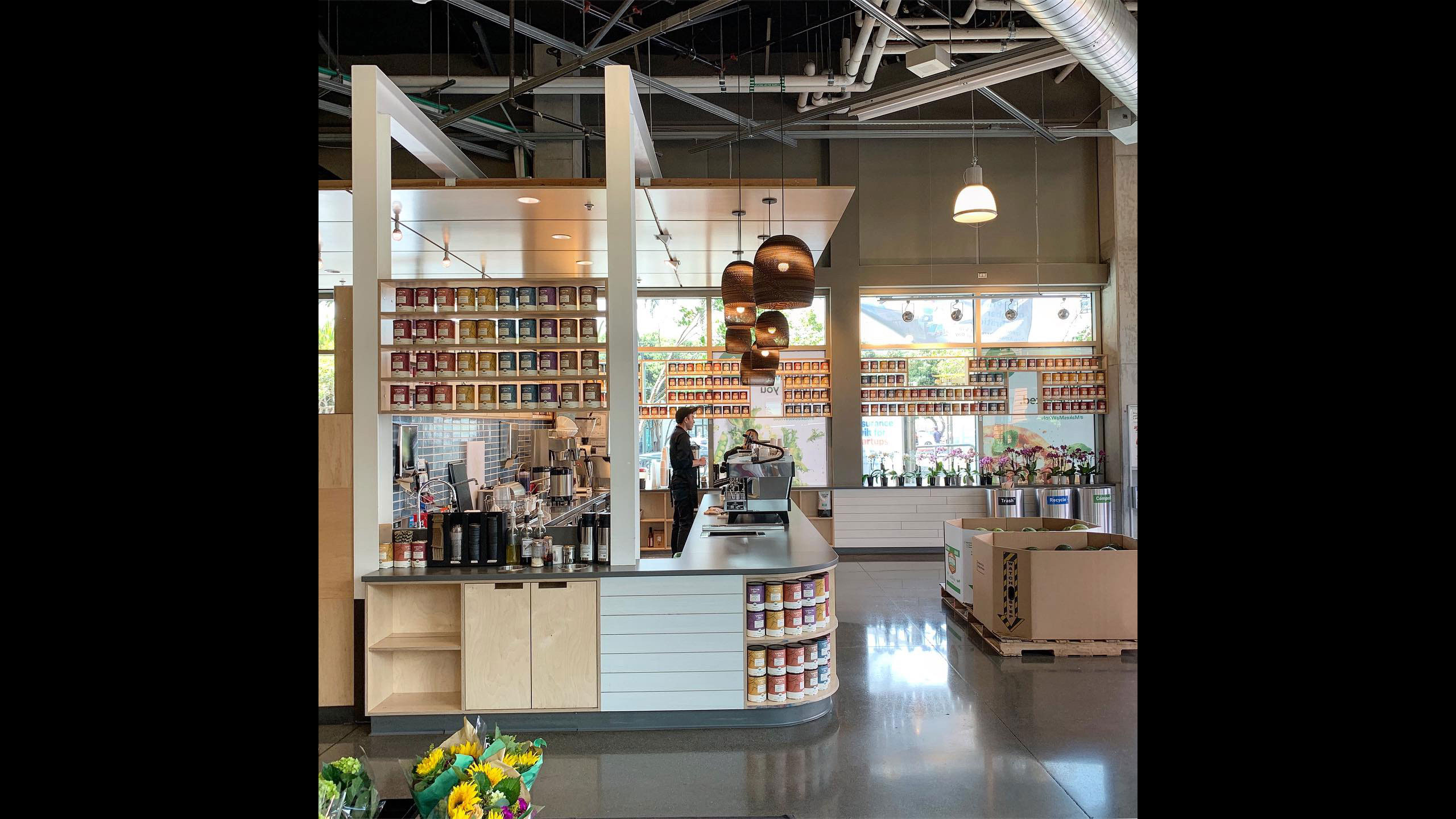 Coffee-Shop-Design-Taylor-Lane-1-Counter-with-dropped-ceiling-brown-light-fixtures-and-open-shelving
